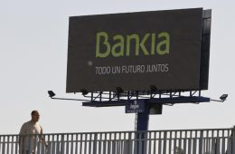 """A man walks past a billboard advertisement for Bankia bank which reads """"Our Future Together"""" in Madrid"""